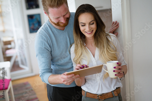 Happy couple using tablet and drinking coffee at home