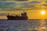 Statek towarowy na zachodzie słońca światła przechodzenia do portu