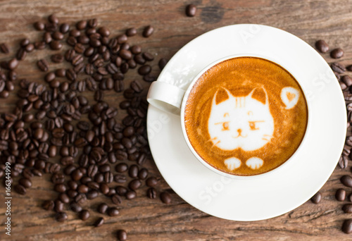 Sticker Cat face design of latte art coffee in white cup on wood table with coffee beans around