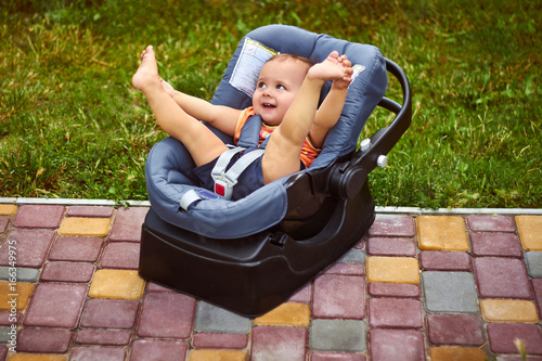 Infant baby seat in modern car seat in a park Poster
