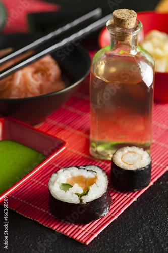 Sushi rolls, wasabi, ginger and vinegar in glass bottle