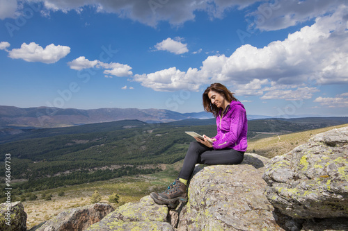 sport hiking or trekking woman with purple jacket, sitting on rock peak, watching digital tablet, next to Lozoya Valley and Guadarrama Park, in Madrid, Spain