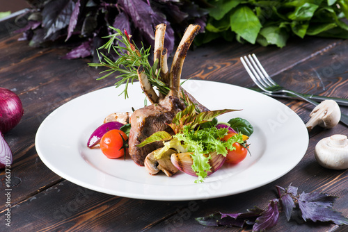 Steak with bones of beef on a wooden background - 166373197