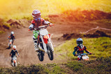 Fototapety Young child racer on a motorcycle participates in motocross cross-country in flight, jumps and takes off on a springboard on the team of rivals. Concept active extreme rest.
