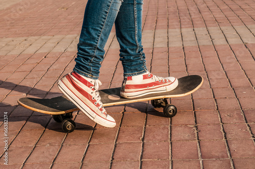 Foto op Aluminium Skateboard Skateboarder legs riding skateboard at street