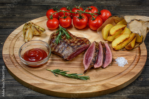 Grilled sliced beef steak with rosemary and tomatoes, on a wooden table