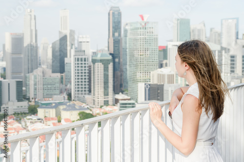 Closeup view of girl enjoying fantastic cityscape from rooftop