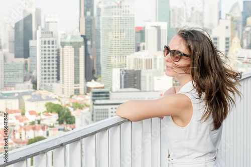 Young woman in sunglasses at rooftop of high-rise building