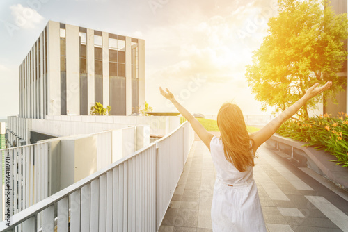 Young woman with raised arms at modern rooftop garden