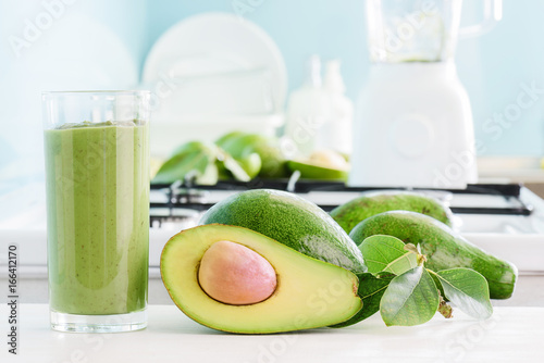 Fresh avocado smoothie and ripe avocados on kitchen table