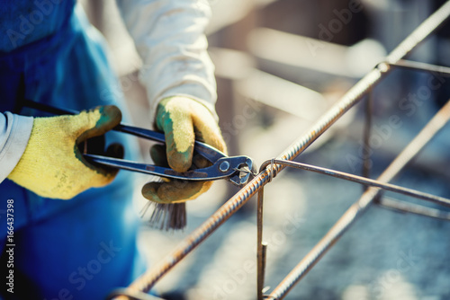 Details of construction workers hands securing steel bars with wire rod for rein Poster