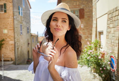 attractive woman tourist with hat in old italian town