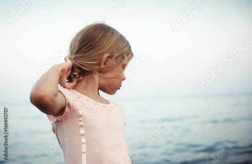 Beautiful girl in fashionable dress touching her hair, posing over blue sea background.