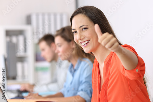 Happy employee looking at you with thumbs up