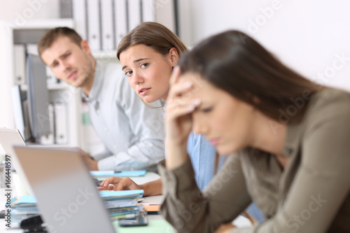 Sad workers looking at a frustrated colleague
