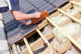 a roofer laying tile on the roof - 166456191
