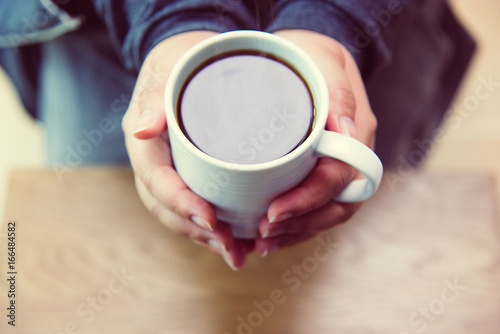 A woman's hand holding a coffee cup on a wooden table top view