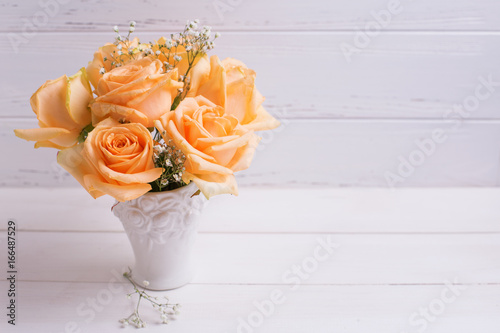 Fresh peach color roses flowers  in white vase on  wooden background.