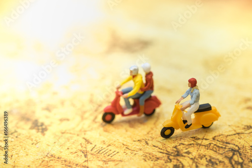 Travel Concept. Group of traveler miniature people figures ride motorcycle / scooter on world map.