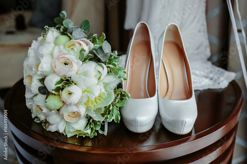 Bouquet of white roses and elegant wedding shoes on wooden table