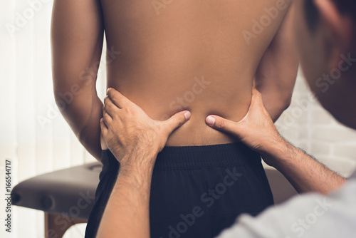 Leinwanddruck Bild Therapist giving massage to back pain patient in clinic