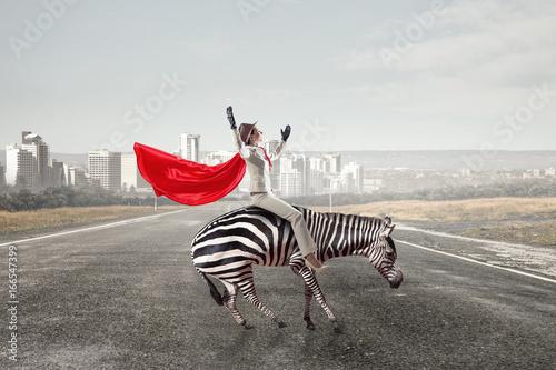 Businesswoman riding zebra. Mixed media