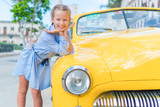 Adorable little girl in popular area in Old Havana, Cuba. Portrait of kid background vintage classic american car