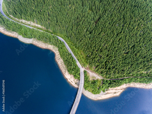 Road bridge over lake and mountain forest aerial view