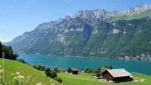 Keuken foto achterwand Bergen Bauernhaus am See/Blick auf den Bergsee Walensee in der Schweiz; die steilen Felswände der Churfirsten und türkisfarbiges Wasser; im Vordergrund eine Wiese mit einem Bauernhaus