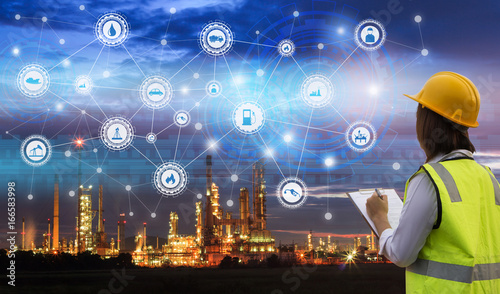 Industry 4.0 concept engineering use clipboard with checking and industrial icons on oil refinery industry sunset background.