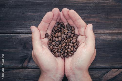 Papiers peints Café en grains Connected hands holding coffee seeds over wooden desks table.