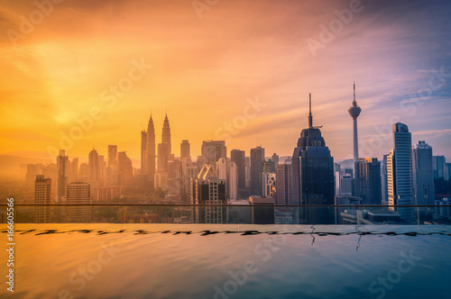 In de dag Kuala Lumpur Cityscape of Kuala lumpur city skyline with swimming pool on the roof top of hotel at sunrise in Malaysia.