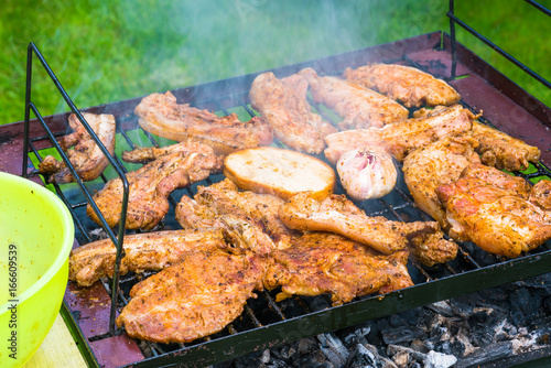 BBQ in the garden - selection of meat on flaming grill © beataaldridge