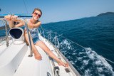Happy young woman sits on deck of the boat sailing in the tropical sea - 166625363