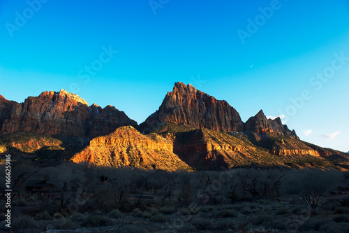 Foto op Canvas Blauw The setting sun shines on cliffs in Zion National Park