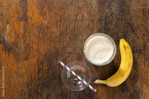 Aluminium Milkshake Banana milkshake in plastic cup on wooden background