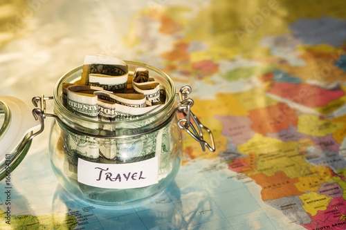 Foto Murales Travel money savings in a glass jar with map in background