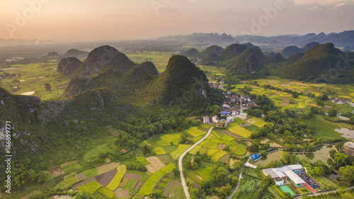 Aerial view of a village surrounded by Padi fields and hills in Guanxi, China