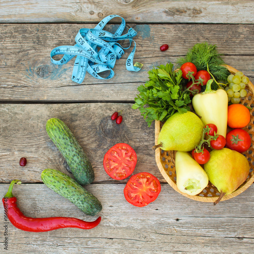Fruits, vegetables, measure tape on wooden background. Top view.