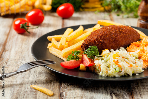 Foto op Plexiglas Kiev Chicken Kiev (de Volaille chop) with french fries and salads.