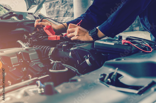 Sticker Auto mechanic checking car battery voltage