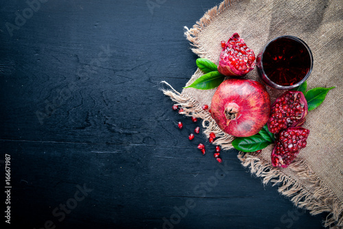 Fresh pomegranate on a dark Wooden surface. Top view. Poster