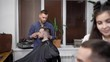 Male barber working with client covered with cutting cape shaping perfectly his haircut with comb and scissors. Female hairdresser using electric trimmer for making modern hairstyle of handsome man.
