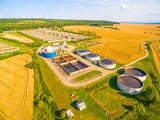 Aerial view to biogas plant from pig farm in ripe wheat fields. Renewable energy from biomass. Summer on countryside. Modern agriculture in European Union. - 166699984