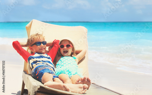happy little boy and girl relaxed on summer beach