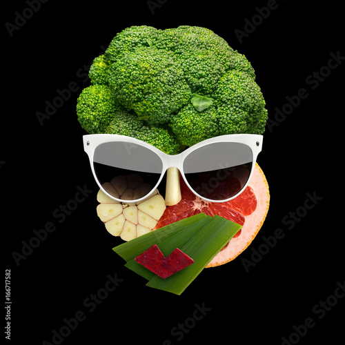 Tasty art /Quirky food concept of cubist style female face in sunglasses made of fruits and vegetables, on black background. - 166717582