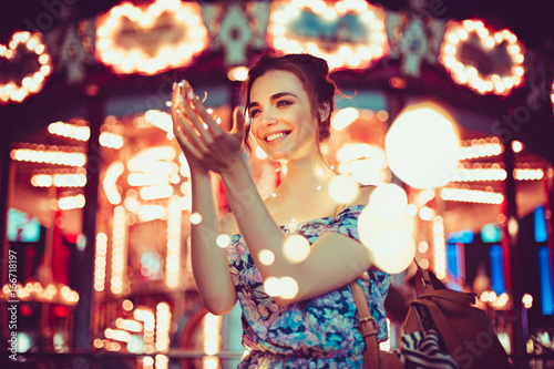 Wall mural Beautiful young woman smiling and talking garlands of lights at city