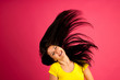 attractive young woman listens music over pink background