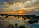 Zachód słońca nad morzem, kamienie na pierwszym planie