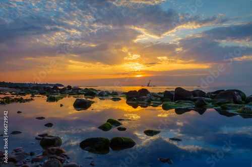 Sunset over the sea, stones at foreground